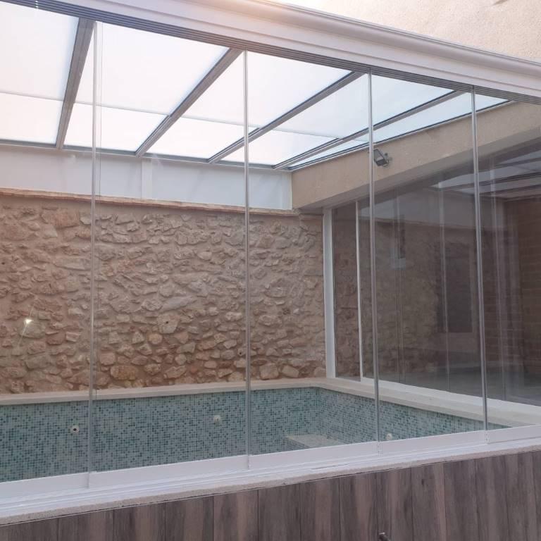 Cerramiento en piscina con cortina de cristal y techo movil
