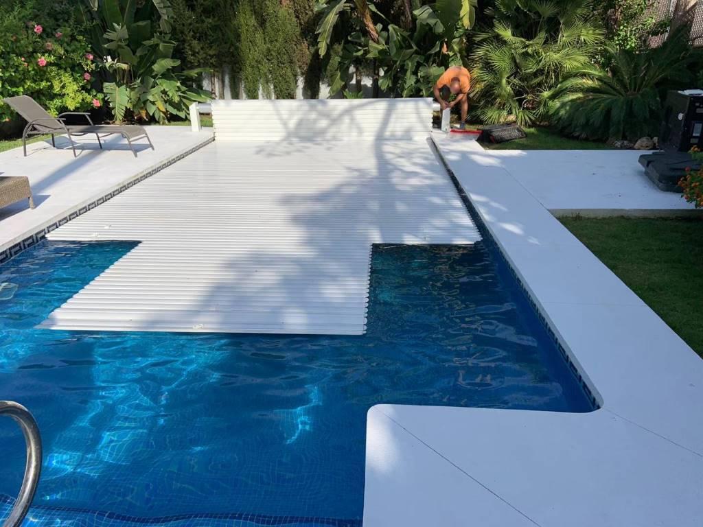 Cubierta de lamas blancas para piscina con escalera romana